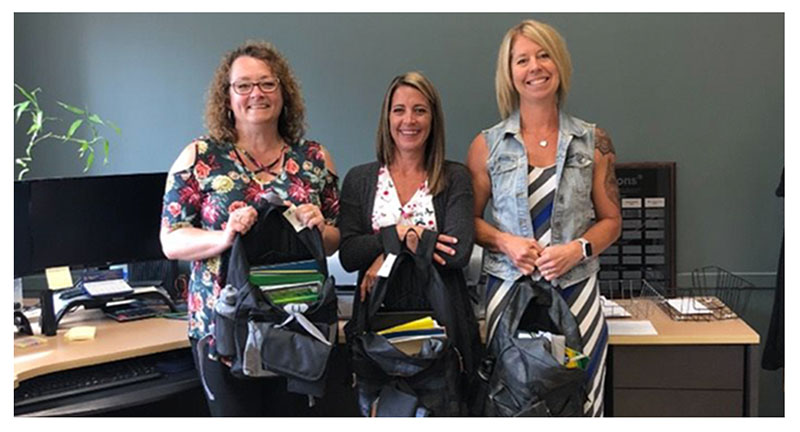 Three of our employees showing backpacks to be donated to kids in our Community.